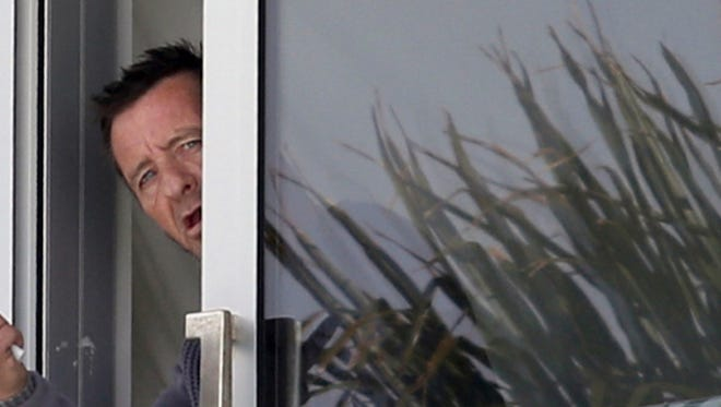 Phil Rudd peeks out of his house and flips off photographers.