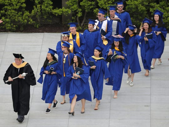 The first graduates enter the stadium as the University of Delaware hosts commencement ceremonies for approximately 6,200 degree recipients at Delaware Stadium Saturday.