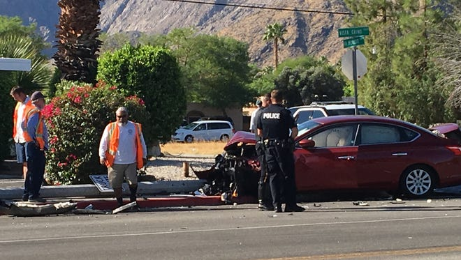 Road crews examine a street light that was knocked over after two cars collided at Vista Chino and Via Miraleste in Palm Springs Monday morning.