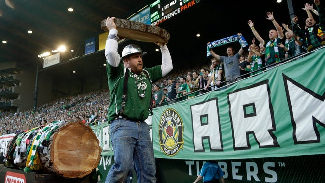 Portland Timbers mascot Timber Joey holds up a freshly cut hunk of log to cheering fans after the Timbers scored during the first half of an MLS soccer game against D.C. United in Portland, Ore., Wednesday, May 27, 2015.  Timber Joey cuts a piece of log for every goal scored.