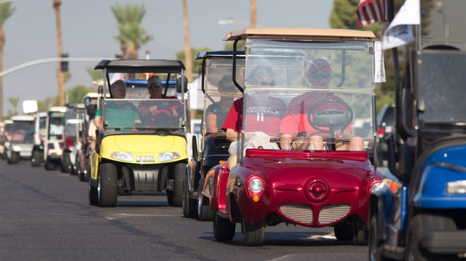 Denny Lockmon drove his red Studebaker golf cart with passenger Mary Ann Lemley in Sun City on Aug. 14, 2014, along with over 100 others to celebrate a new law that allows such vehicles to drive in the shoulder of the road, and stay out of traffic's way, in some areas.