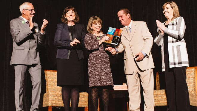Tina Byford, center, chief operating officer for the New Mexico State University Foundation, accepts the Nonprofit of the Year award from last year's winner, Kevin McGrath of Burger Time. Joining them on stage are, at left, Rick Jackson, chair of the Chamber Board of Directors, Leslie Cervantes, NMSU associate vice president for alumni engagement and stewardship, and at right, Denise Tafoya, NMSU director of development.