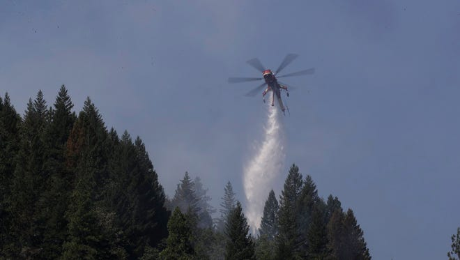 A helicopter drops water during a forest fire west of Dunsmuir.