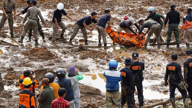 Rescuers remove the body of a victim of landslides that swept away houses in Jemblung village, Central Java, Indonesia, on Saturday, Dec. 13, 2014.
