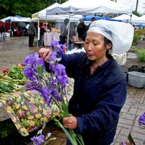 Shoppers wander among the stalls offering a broad range of products at the Tosa Farmers Market.
