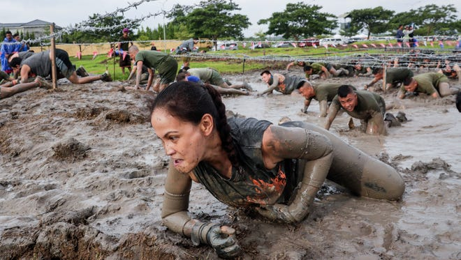 Participants crawl through mud under barbed wire during the Tough Mudder event in Alabang, south of Manila, Philippines.