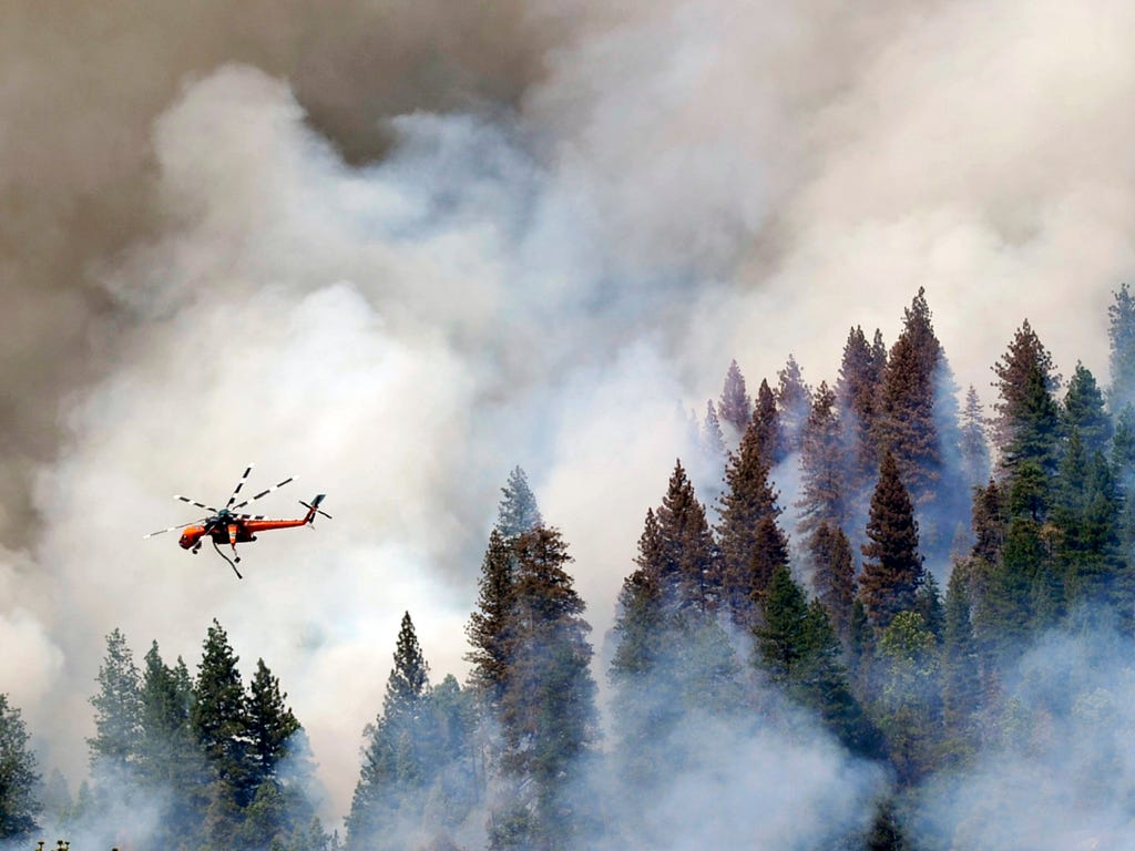 A helicopter flies over Willow Creek Canyon as a wildfire continues burning in the Sierra near Bass Lake, Calif.