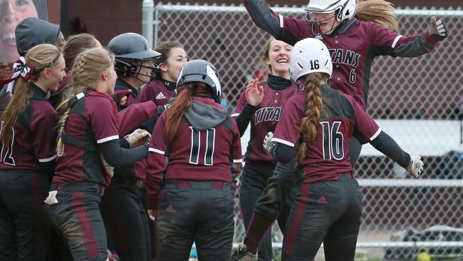 Greece Arcadia's Ericka Dwyer leaps onto home plate, surrounded by her cheering teammates, as they celebrate her two-run home run in the fifth inning against Brockport. Arcadia beat Brockport 5-1.