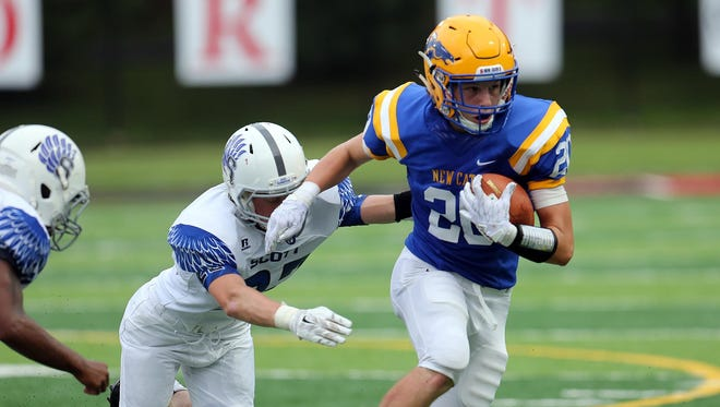 Newport Central Catholic wide receiver Ian Dew breaks a tackle against Scott.