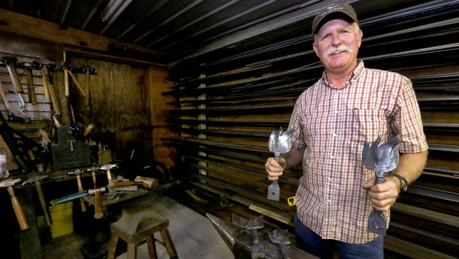 Joe Brown shows off the hand-crafted awards he created from pieces of the Statue of Liberty in his shop, Brown View Farm & Forge, in Readyville, Tenn.