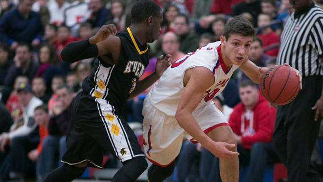 Dan Masino of Fairport dribbles past Shawn Gaines of Greece Athena during a game at Fairport High School on Saturday, January 3, 2015.