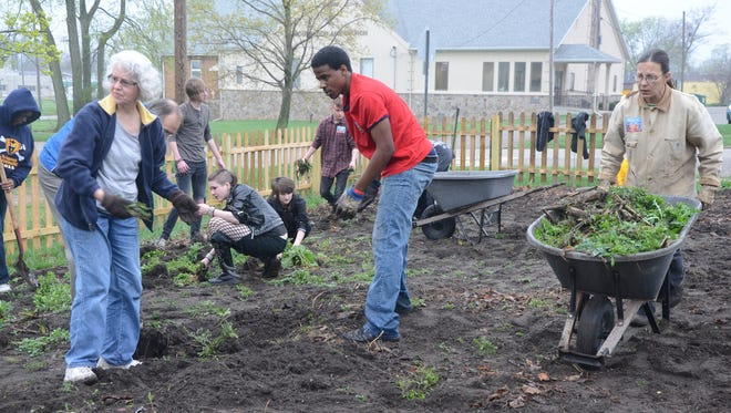 In this 2011 photo, about 20 people work on the Patch of Heaven Community Garden behind Mt. Zion AME Church.
