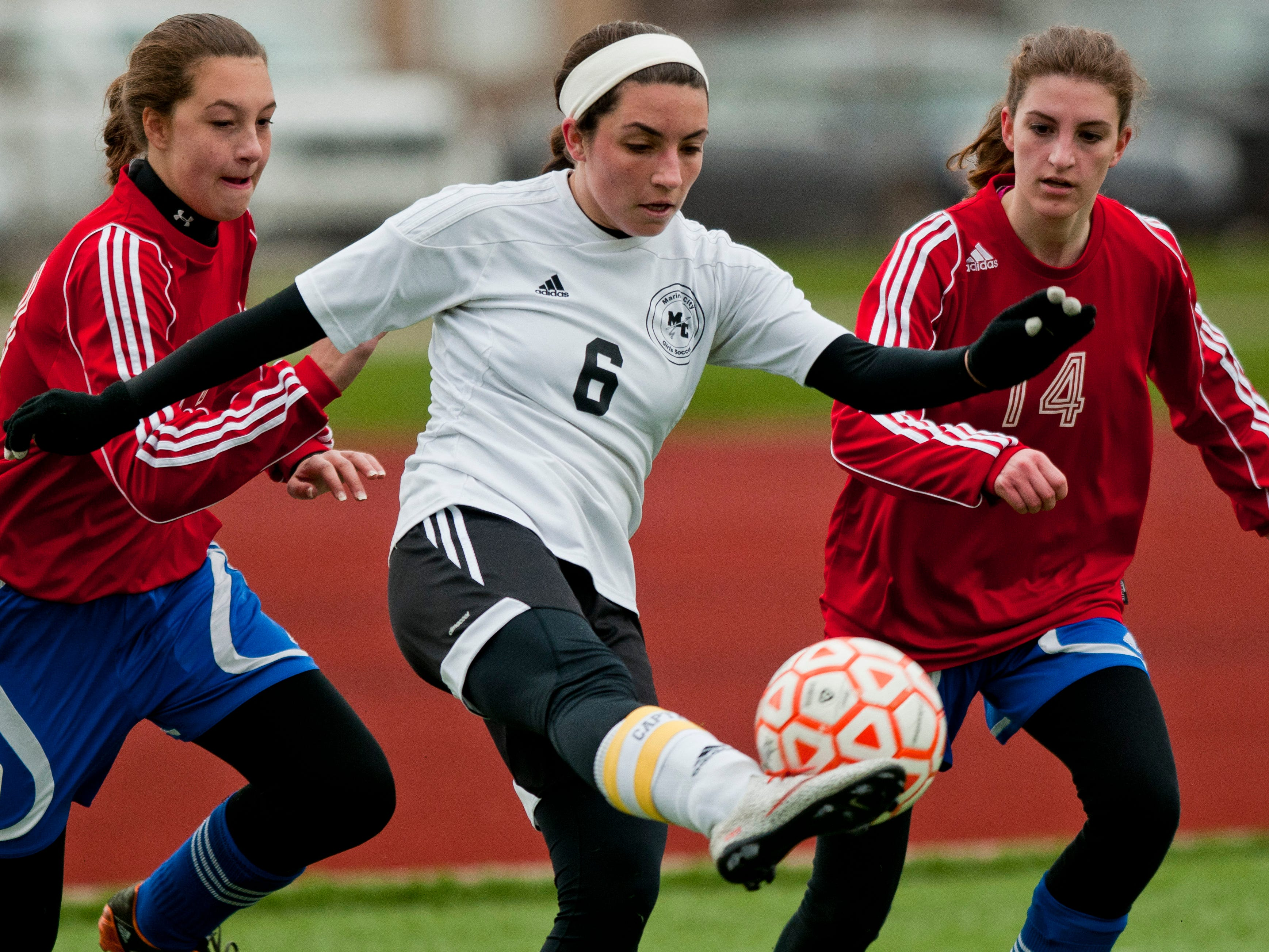 Marine City's Olivia Viney attempts to clear the ball away from St. Clair defenders during a soccer game Wednesday at East China Stadium.