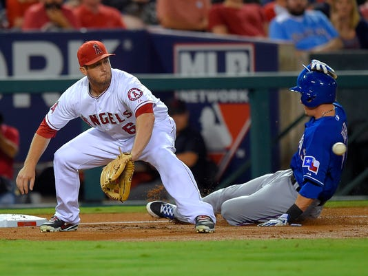 Texas Rangers' Ryan Rua, right, slides in safely at third on a single by Rougned Odor as Los Angeles Angels third baseman David Freese waits for the throw during the second inning of a baseball game, Friday Sept. 19, 2014, in Anaheim, Calif. (AP Photo/Mark J. Terrill)