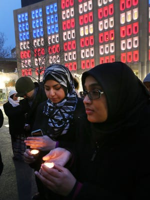 Noor Ayesha, left, from Ball State, and Samreen Uzzama, from Butler University, hold candles on Monument Circle during a moment of silence for the three Muslim victims of a shooting in Chapel Hill, North Carolina Monday, February 16, 2015. Students from the Muslim Student Association at IUPUI organized the vigil to show support for the victims of last week's shooting.
