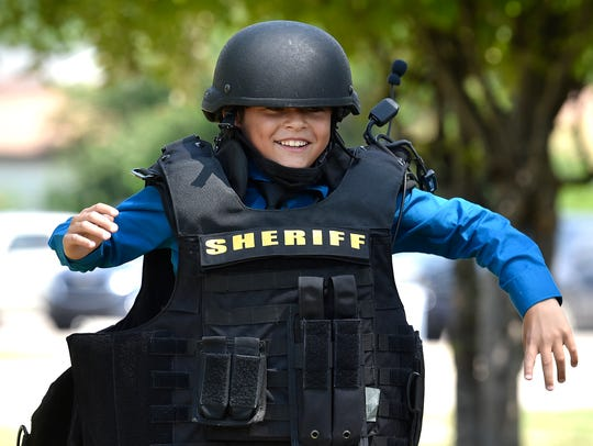 Camp Care attendee Isaiah runs wearing SWAT gear weighing 30 pounds.
