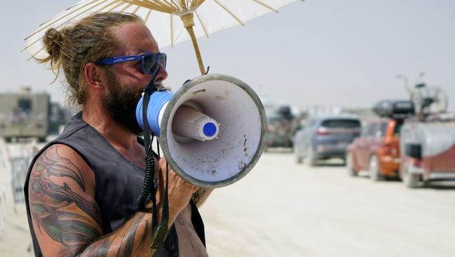 Mike Orwell, 31, of Chicago, calls out to passing drivers as cars, trucks and RVs slowly drive out of Burning Man on Sunday afternoon. Orwell, who works for the Department of Public Works at Burning Man, was asking drivers to donate unwanted food, booze and cigarettes to Burning Man workers who are rstaying behind for the next month to remove all traces of the city from the desert.