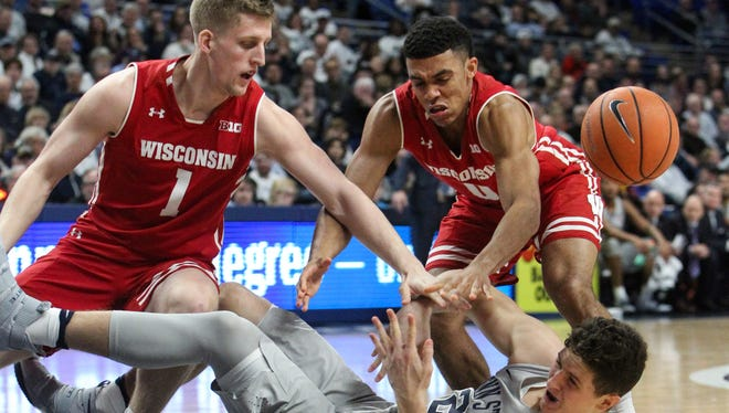 Wisconsin guards Brevin Pritzl (left) and D'Mitrik Trice and Penn State forward John Harrar  fight for a loose ball Monday night.