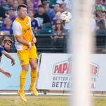 Louisville City FC midfielder Charlie Adams tries to kick a goal as Pittsburgh Riverhounds' Ben Newnam grimaces. 29 Aug 2015
