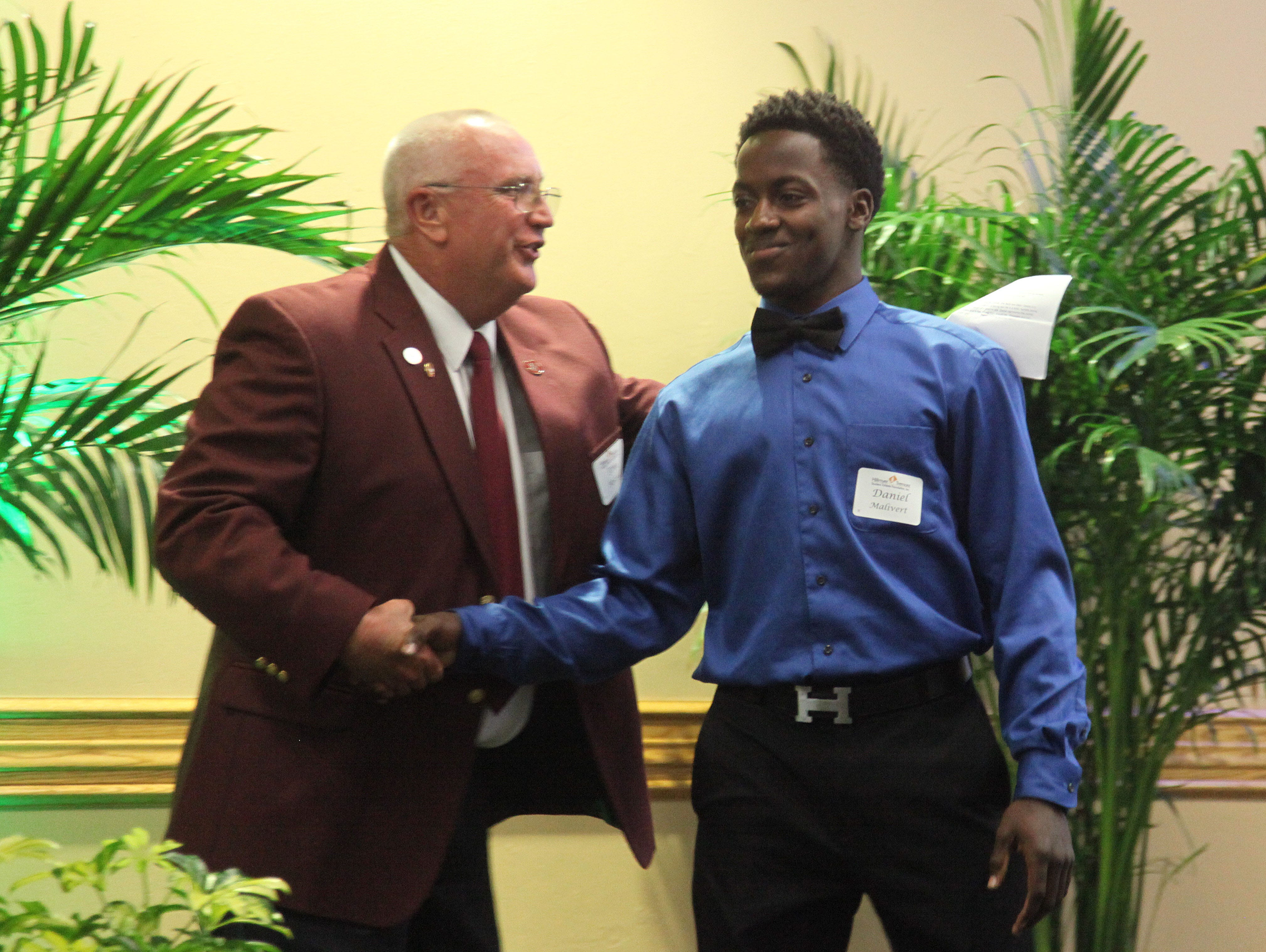 Daniel Malivert, of Riverdale High School, is congratulated by coach Tom Roszell during the Hillmyer-Tremont scholarship banquet at FGCU's Cohen Center on Monday.
