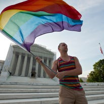 Vin Testa waves a rainbow flag at the Supreme Court in 2013.