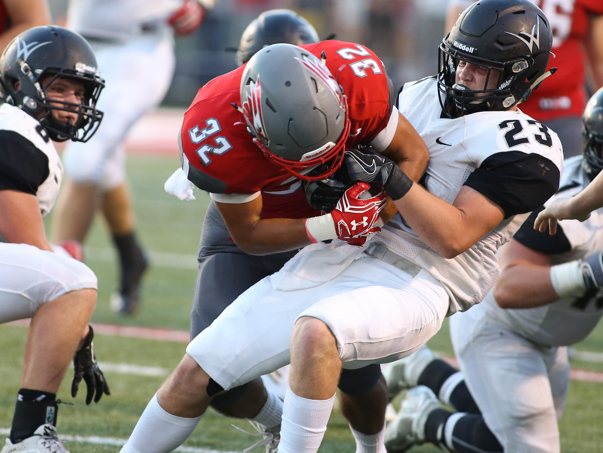 Willard High School's Clay Burkett-Gibson tries to rip the football away from Nixa's Nicos Oropeza Friday, August 19, 2016. Jason Connel / For the News-Leader
