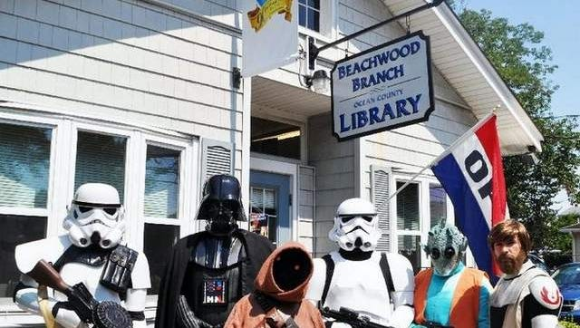 """Members of the Star Wars fan club of Vader's 501st Legion wearing costumes from various Star Wars films stand in front of the Beachwood branch of the Ocean County Library during Saturday's """"Star Wars"""