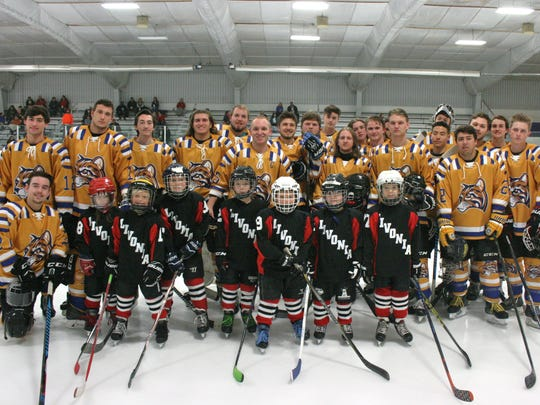 Before the start of Saturday's game at Redford Arena, Schoolcraft College hockey players posed with seven players from the Livonia Timbits Mites team for a group photo.
