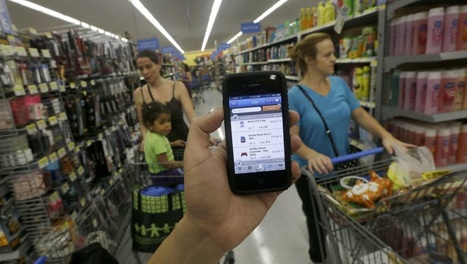 A Walmart representative demonstrates a Scan & Go mobile application on a smartphone at a Walmart store in San Jose, Calif., Thursday, Sept. 19, 2013.