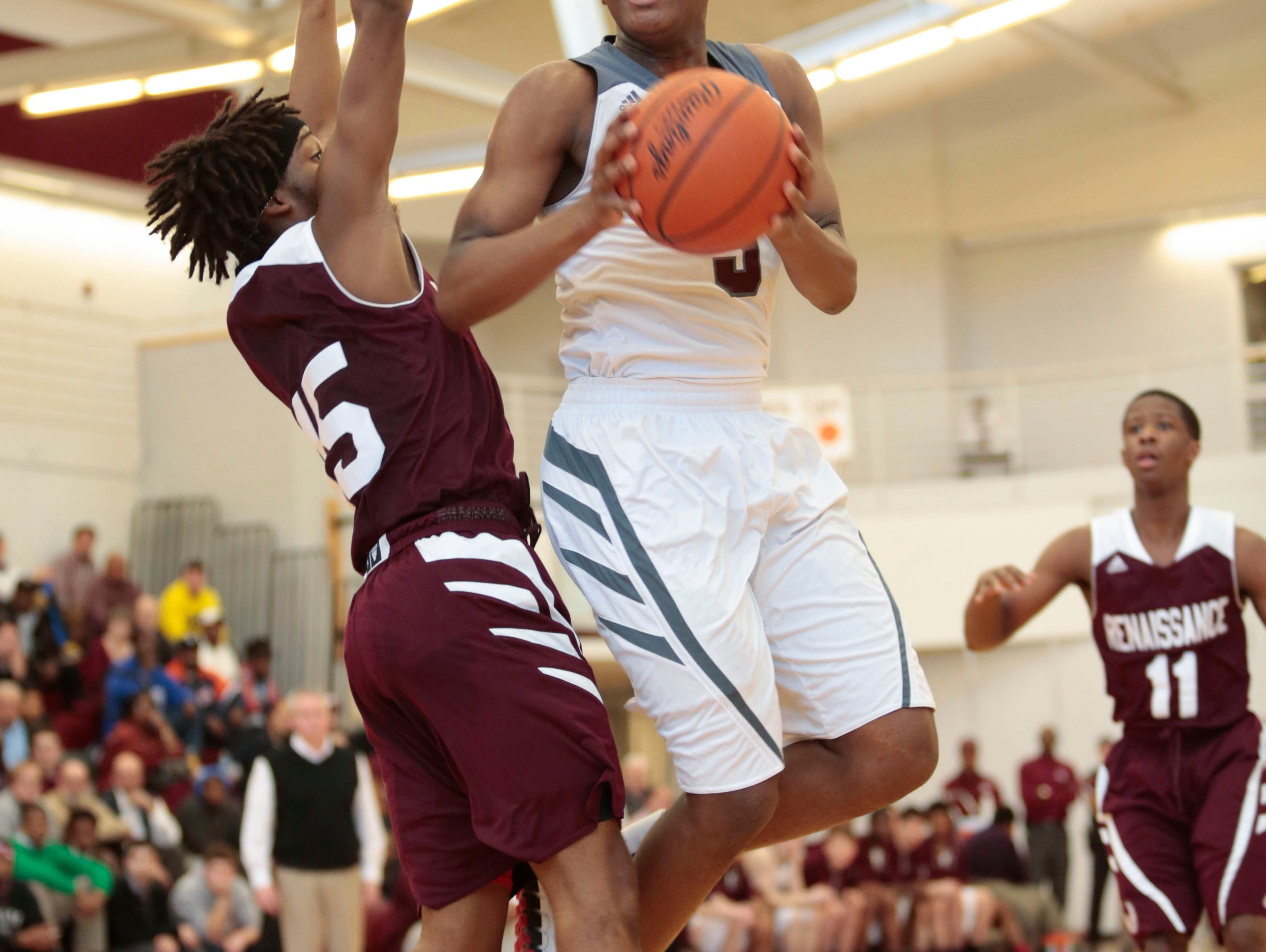 Renaissance's Darryl Smith (15/G) tries to block a shot by U of D's Cassius Winston (5/G) during the Detroit Renaissance vs, U of D Jesuit district semi-final boys' basketball game on Wednesday, March 11, 2015 at Detroit Renaissance High School in Detroit. U of D Jesuit beat Detroit Renaissance 66 to 53. Tim Galloway/Special for DFP