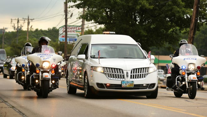 A motorcade escorts the hearse to Cintas Center for the funeral. Cincinnati Police Officer Sonny Kim was killed Friday, June 19, by Trepierre Hummons, 21, in Madisonville. Kim, a 48-year-old father of three, is the first Cincinnati officer killed in the line of duty since 2000.