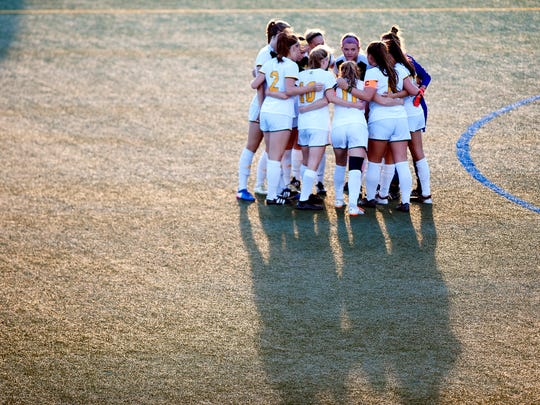 The University of Vermont women's soccer team huddles before its game against Sacred Heart on Friday night at Virtue Field.