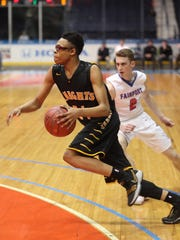 McQuaid's Jermaine Taggart drives past Fairport's Tommy