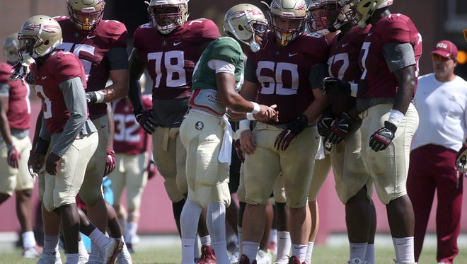 FSU's Deondre Francois huddles up with his teammates during practice at the Dunlap Training Facility on Monday afternoon.