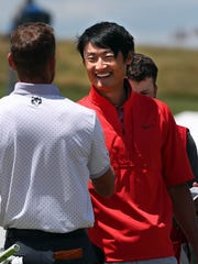 Haoong Li of China manages to smile after rough third and fourth rounds during the U.S. Open at Erin Hills