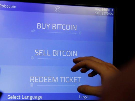 Christopher David uses a Robocoin kiosk to sell bitcoins