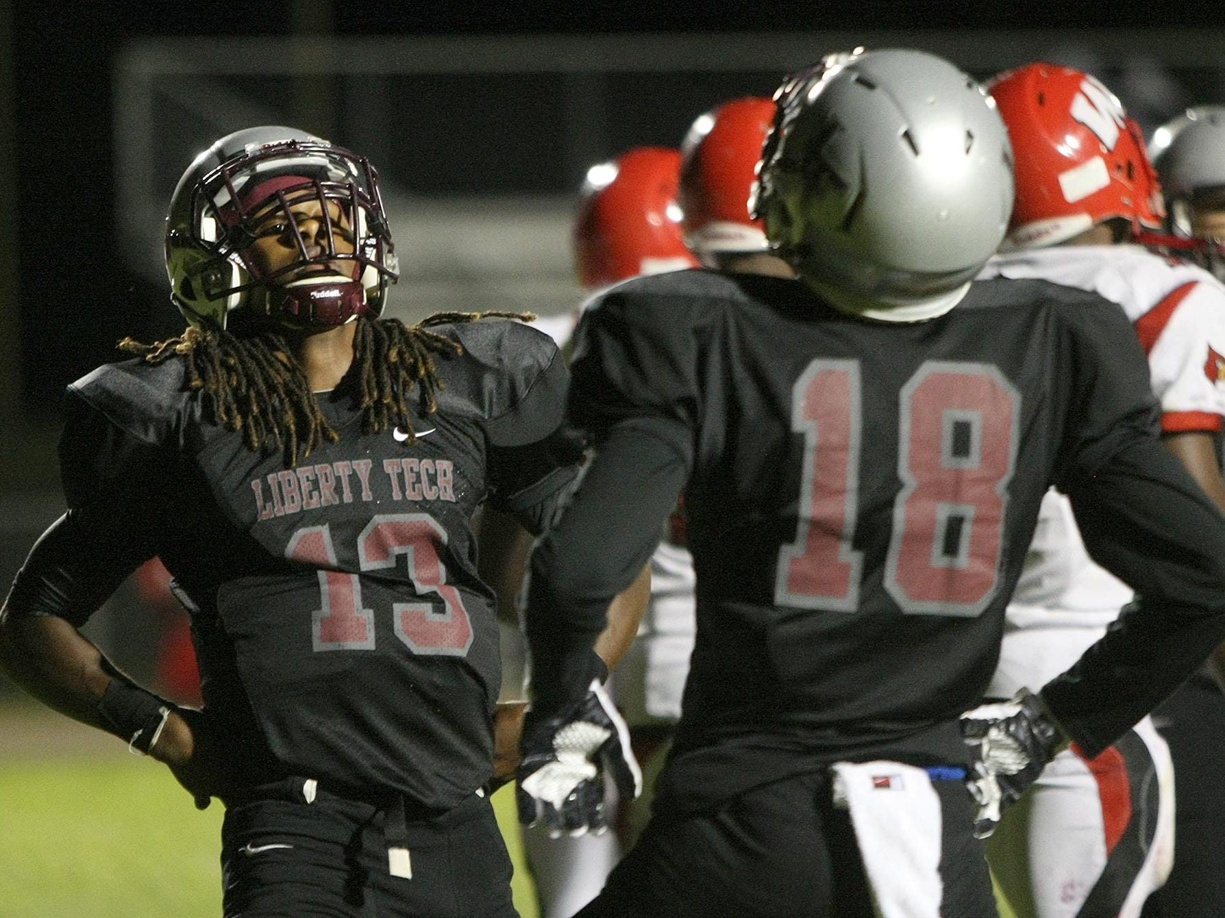 Liberty's Corey Newble (13) and Rodney Castille (18) celebrate Newble's touchdown against Wooddale at Liberty High School Friday.