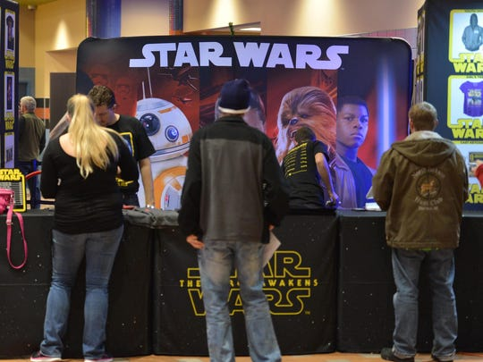 """Movie fans buy Star Wars merchandise before the first showing of """"Star Wars: The Force Awakens"""" on Thursday at MJR Digital Cinemas in Troy."""