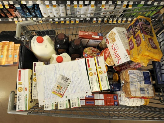 Coupons rest on top of Annette Spain's shopping list in her cart at the Kroger on University .