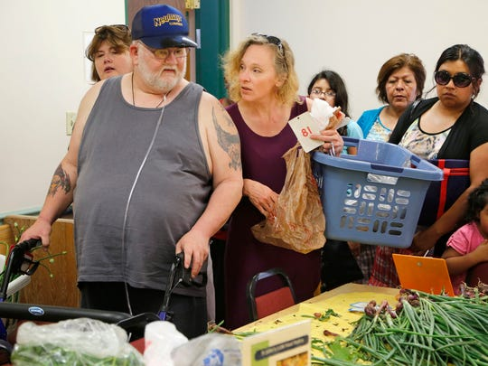 Cathy Collins assists Carl Rohland as he makes his food selections at the first St. John's/LUM weekend food pantry on June 7 at St. John's Episcopal Church, 600 Ferry St.