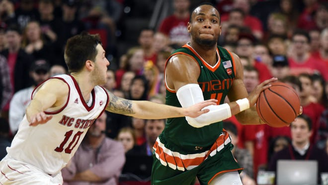 Miami (Fla.) guard Bruce Brown Jr. looks to pass while being defended by North Carolina State's Braxton Beverly.