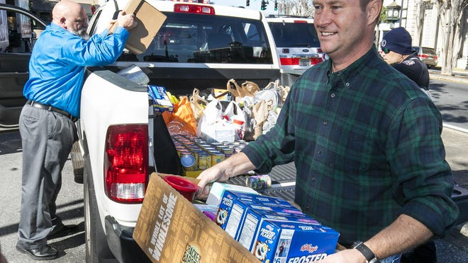 Greg Harrell, foreground, carries a box of dry goods from a pickup truck during a recent food drive. Harrell will be the next Marion County Clerk of Court to replace David Ellspermann, who is retiring.