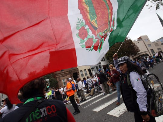 Lily Loyola, of Mexico, waves an Our Lady of Guadalupe flag.