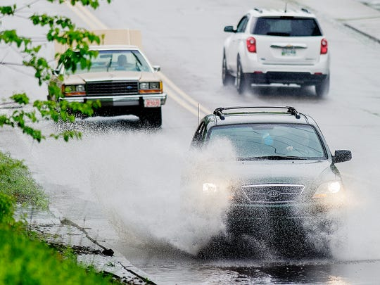Vehicles drive through a large puddle of water along