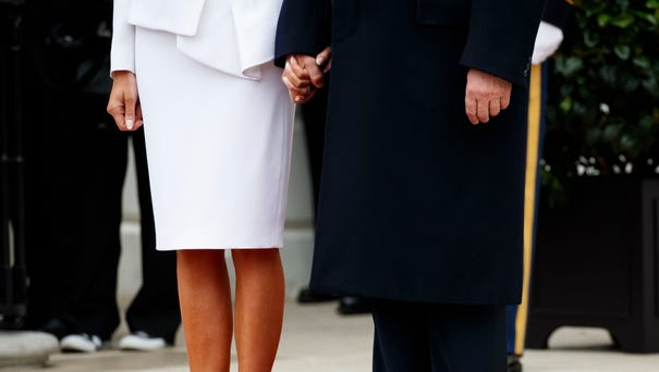 President Trump and first lady Melania Trump hold...