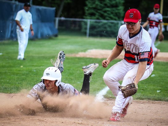 Plymouth's Evan Good (left) scores on a wild pitch as John Glenn pitcher Chad Stevens (right0 covers the plate.