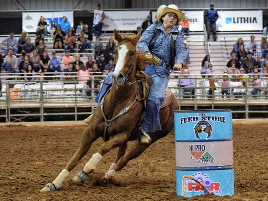 New Mexico State University Rodeo athlete Eva Belzil competes in the barrel racing event at the Las Cruces, New Mexico rodeo.