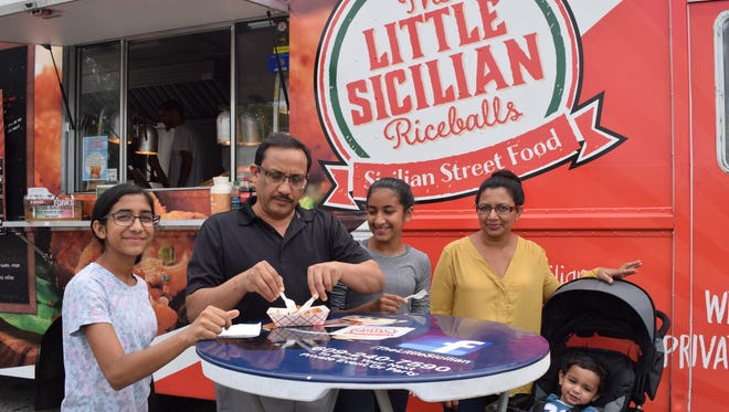 The Elahi family, from left, Ruth, 13, Ron, Zara, 14, Mona, and Samual, 1, of Vineland, share a snack from The Little Sicilian Riceballs during the Food Truck Fest on the Ave.