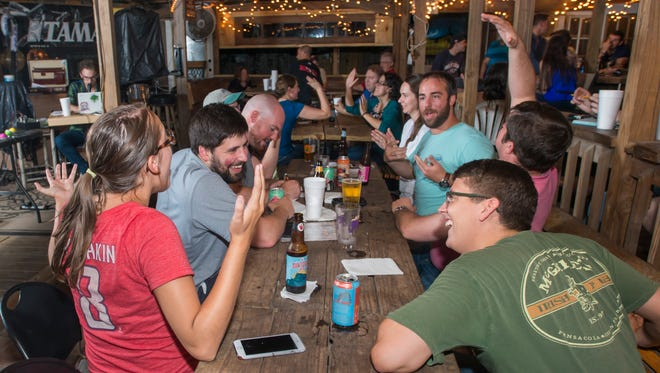 Team E=mc Hammered celebrates a correct answer during trivia night at the Goat Lips Chew & Brewhouse in Pensacola on Wednesday, June 13, 2018.