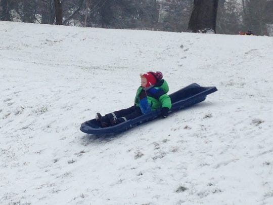 "A young sledder enjoys a morning on Glenwood Hill Wednesday, ending each run with ""Do it again!"""